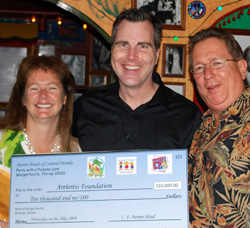 Lisa and George Schott presenting check to Arthritis Foundation